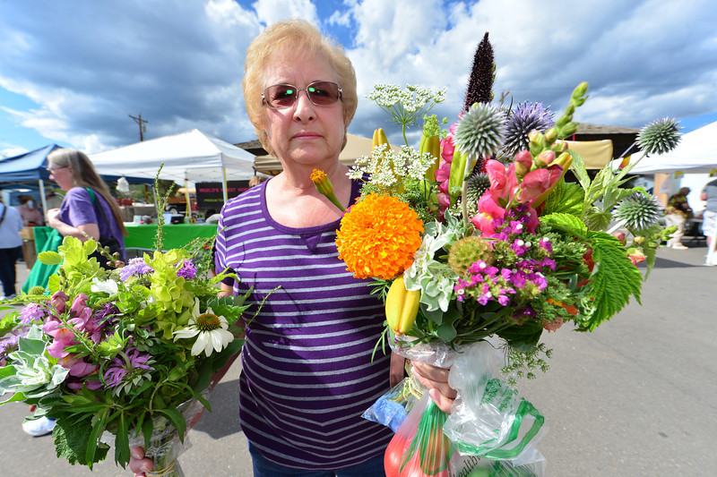 "Shelm Lustig of Estes Park carries off a double-fistful of flowers at Thursday's Estes Valley Farmers' Market. ""Best move we've ever made,"" said Lustig of her familie's migration to Estes Park."