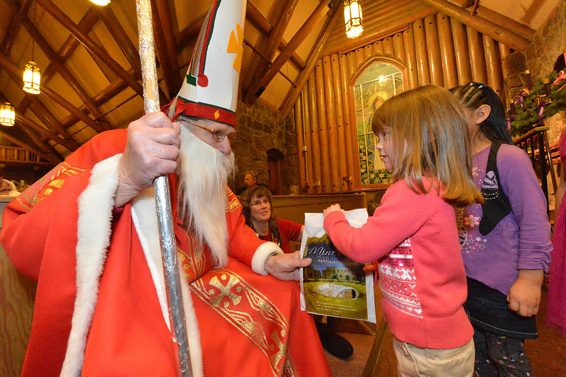 Saint Nicholas hands out gift bags to the children at the pageant on Sunday. The arrival of teh good saint is the highlight of the evening for the children.