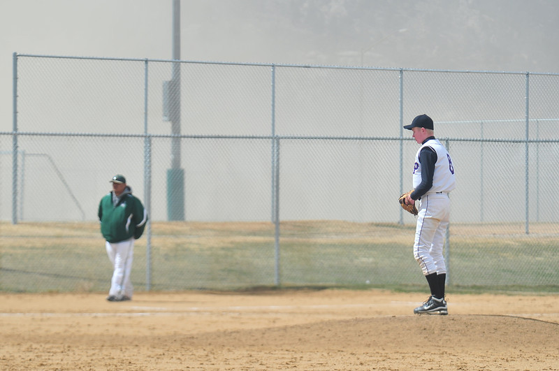 Dylan Jirsa stands atop the mound in his brief and dusty appearence during the 'Cats doubleheader against Highland on Saturday. High winds blew dust around the fields at Stanley Park on Saturday.