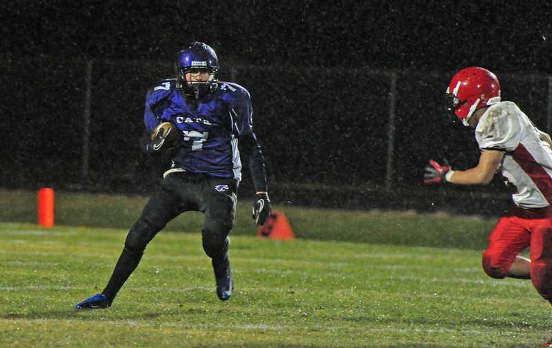Adam Christianson confronts a Jefferson tackler as rain falls on Friday. The Bobcats fought hard but could not overcome the Saints, losing 41-24.