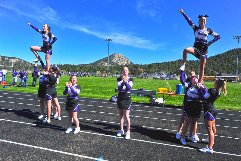 Cheerleader entertain the fans against the backdrop of the brilliant blue sky. The rare day game gave the visiting Platte Canyon team the opportunity to return home in day light.