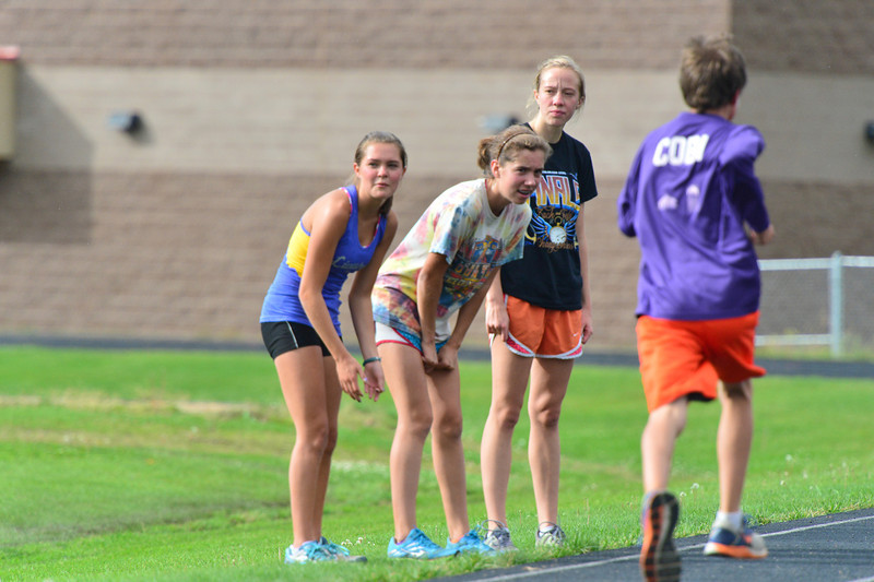 A few of the top girls cheer as the boys run by. The team began the season with a time trial that showed vast improvement over the times posted a year ago.