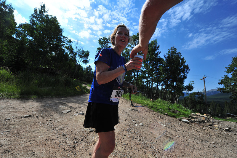 A runner appreciates some rehydration before finishing up the Aspen Climb trail race on Sunday.