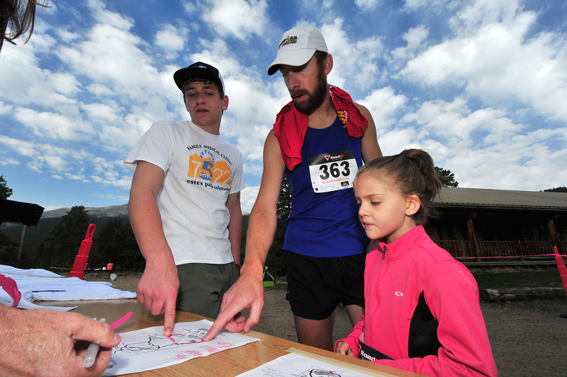 Runners go over the trail map with Peter Koschnitzke at the start line of the Aspen Climb trail run on Sunday.