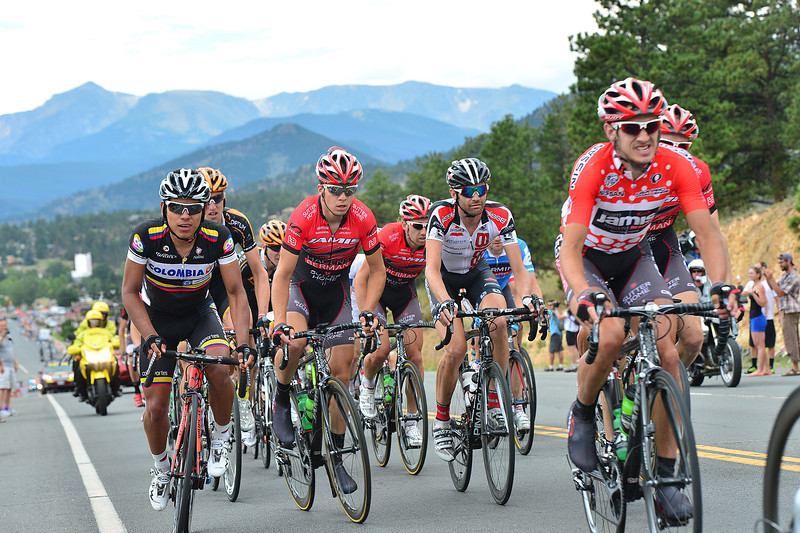 Matt Cook, right, weres the red King of the Mountains jersey as riders speed away from Estes Park on Saturday. If the stage seemed fast to roadside observers, it was: riders averaged over 27 mph over the 115-mile stage.