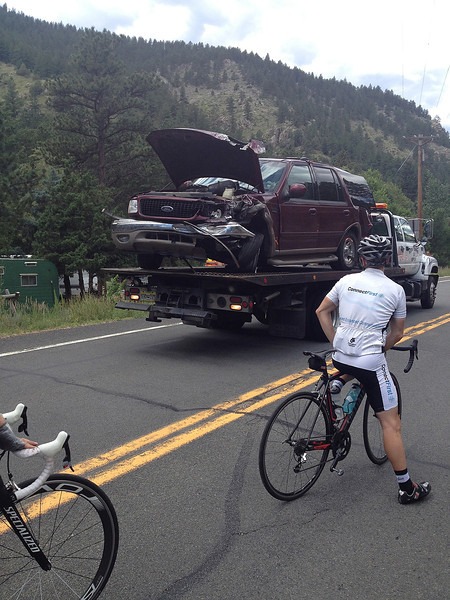 Cyclists watch as one of three vehicles involved in a Sunday morning accident are hauled out of the Big Thompson Canyon. Multiple injuries were reported and unofficial reports suggest one vehicle crossed a double yellow center line just below Drake to pass when the accident occured.