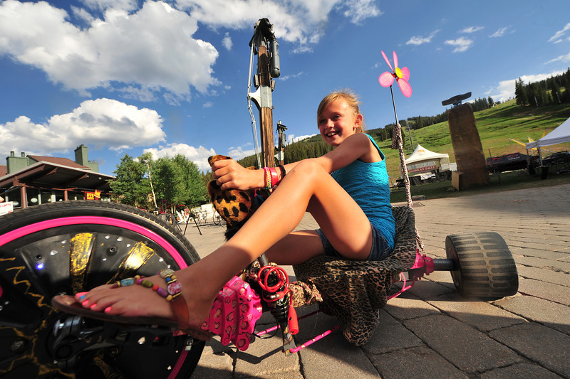 A young rider scoots around Burning Stones Plaza in Copper on a well-decorated tricycle on Sunday. Although riders spend several hours riding through the weekend, the event is fun, and riders have plabty of time to enjoy each others company and find other diversions for a laugh.