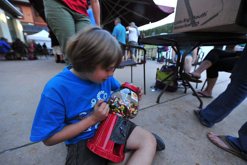Owen Simpson, 9, of Denver, holds a gumball machine full of Jelly Belly jelly beans at the riders' reception on Friday night. Owne sold $500 worth of waterbottles full of Jelly Bellys for his team, Jelly Belly for Kids.