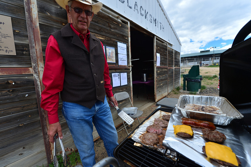 Dennis Pettitt of Estes Park flips burgers on behalf of the Estes Park Western Heritage and the Rooftop Rodeo on Saturday. The committee hosted the start of the Beat the Heat Barrel Racing Series on Saturday and Sunday at the Stanley Fairgrounds.