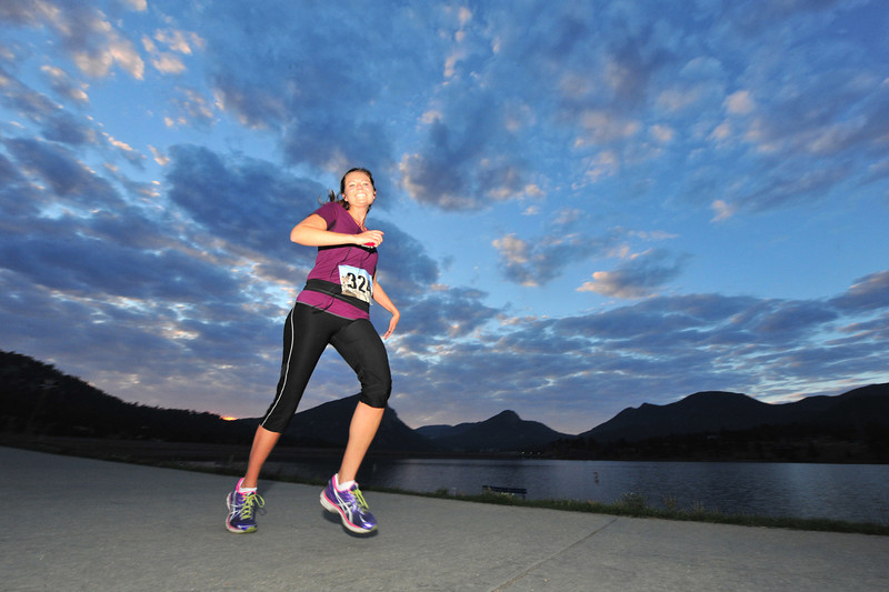 A runner still smiles early on Saturday as she runs past the Lake Estes Marina during the Rocky Mountain Half Marathon. The race started at 6 a.m., affording runners a race without the heat of the day, and a front-row seat to the sunrise.