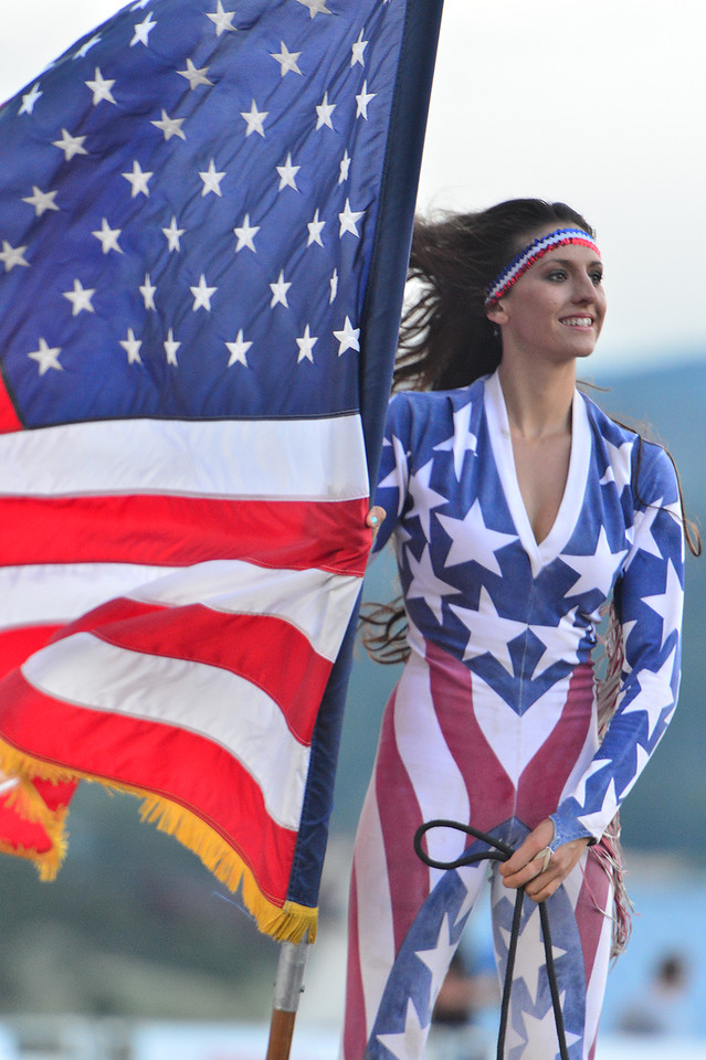 Brandi Phillips holds Old Glory arround the rodeo arena on Friday. Pillips, one of the Riata Ranch Cowboy Girls, had the honor of carrying the flag for the opening ceremonies on Friday Night.