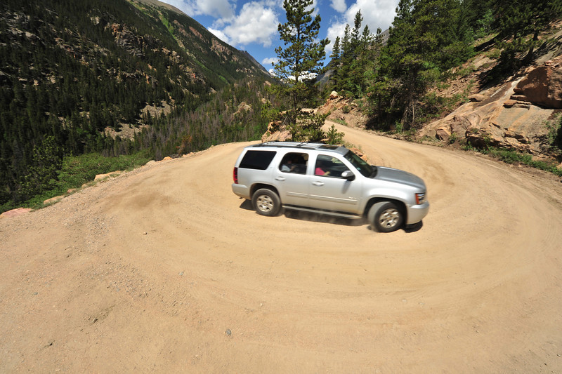 An SUV negociates the tight switchback on the old road. The Old Fall River Road has 16 switchbacks on the narrow, one-way route.