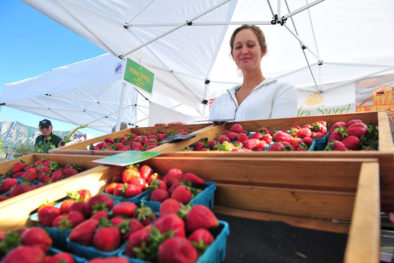 Amy Kafka of Fort Collins beams at her crop of strawberries at the Estes Valley Farmers' Market on Thursday. More fruit is rolling into the market as the season rolls on to autumn.