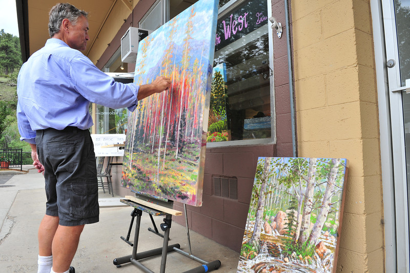 Jim Edkins paints in front of his gallery along Elkhorn Avenue on Sunday. The painter recently opened his galley in a space that has hosted several small galleries.