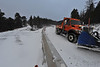 A snow plow leads traffic along a new stretch of Bear Lake Road on Monday. The old route, on the left, will be repurposed as a hiking trail.