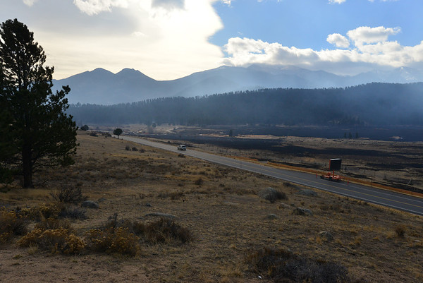A national park vehicle drives south on Bear Lake Road Saturday morning following a wind-driven expansion of the Fern Lake Fire. Much of Moraine Park was blacked by the wind-driven flames overnight.