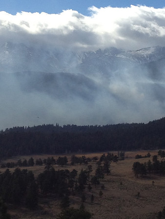 The fire from Trail Ridge Road . Hard to see but there is a helicopter just above the tree line surveying the fire