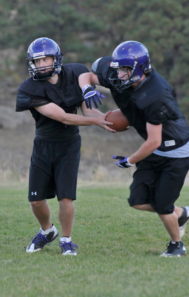 Photo by Walt Hester<br /> Quarterback David Klein reads the defense while back Ty Holler prepares to take the handoff during Monday's practice. Coach Urban is simplifying the Bobcats' offense to allow the 'Cats to perfect a few plays before introducing anything new.
