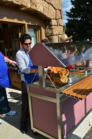 Pancakes fresh off the griddle are added to the serving line Thursday morning during the July 4 Crossroads Ministry pancake breakfast held in the Parking lot of Our Lady of the Mountains Catholic Church.