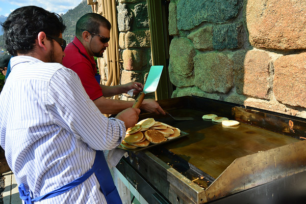 Cooks remove pancakes from the griddle Thursday morning during the July 4 Crossroads Ministry benefit pancake breakfast held in the parkin glot of the Our Lady of the Mountains Catholic Church.