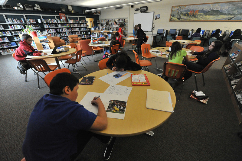 Art students quietly create in the middle school library on Wednesday. The artists took photographs and filled in the rest of the scene, what is not in the photo image, to create something new.