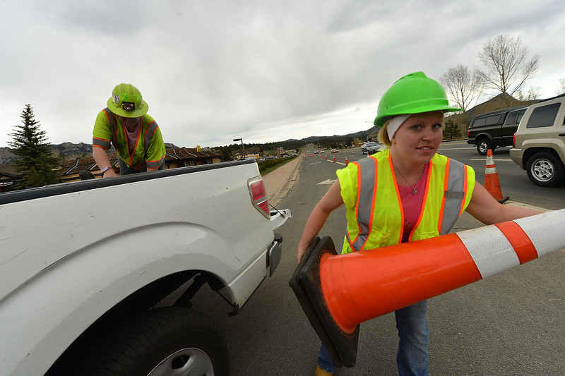 Stephany Salazar and Ashley Nail, both from Greeley, remove cones from a work zone at the intersection of highways 34 and 36 on Wednesday. CDOT is installing signal poles and mast arms, as well as curb ramps, curbs and gutters at the intersection.