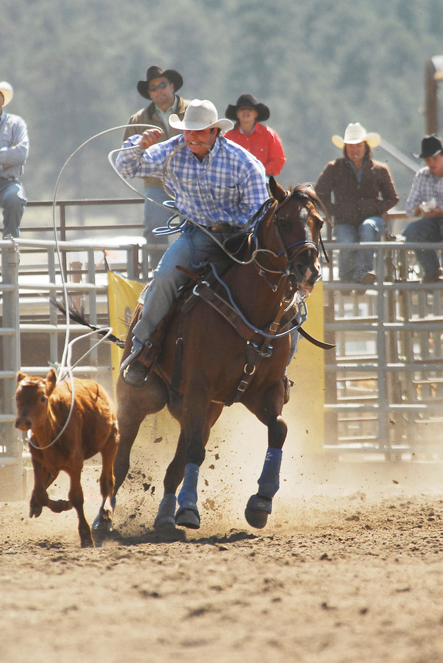 Photo by Walt Hester<br /> Kyle Dickens of Loveland, hits his mark in the Boys 14-18 Tie Down Roping on Sunday.