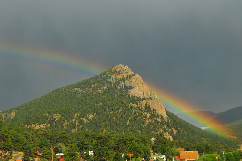Photo by Walt Hester<br /> A rainbow follows a rain squall over Mount Olympus on Saturday. The cool, wet summer trend seems to be continuing through the week.