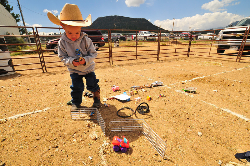 Photo by Walt Hester<br /> Braxton Hamblen, 2, of Ault, CO plays with toy ranch impliments during Saturdays round of the Colorado Junior Rodeo Association Finals at the Stanley Fair Grounds.