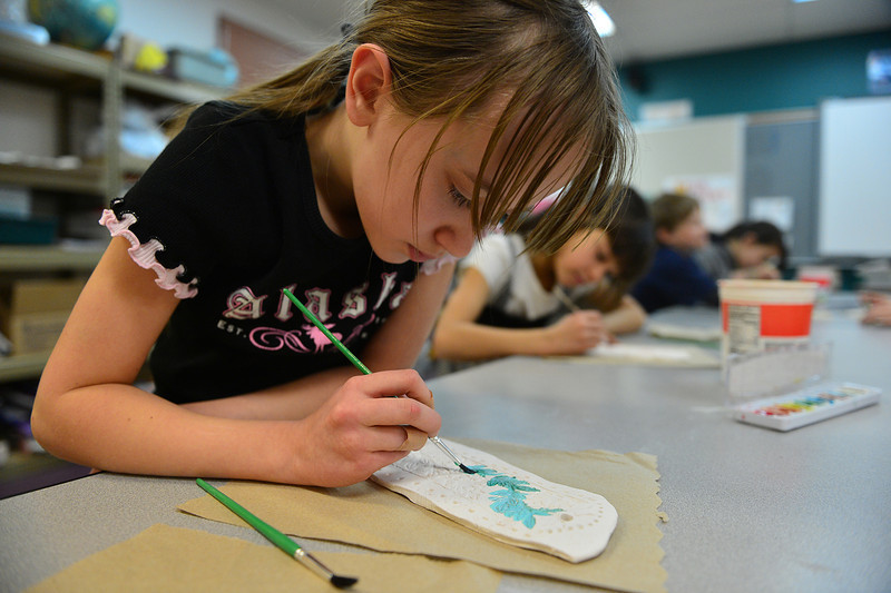 Serena Wendell, 9, paints a stamped wall hanging in art class at the Estes Park Elementary School on Thursday. 'Tis the season for little artists to create artful presents and decorations.