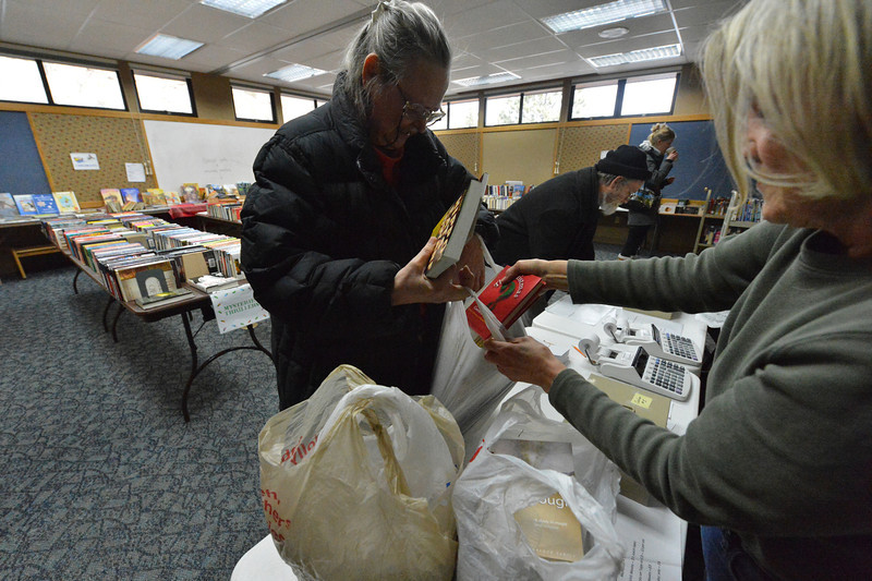 "Judy Smith, left, and husband Kent, pick up some literary presents at the Estes Valley Library on Sunday. The library hosted it's used book sale on Friday and Saturday, giving the public a chance to pick up books, DVDs and other medium in slightly ""loved"" condition."