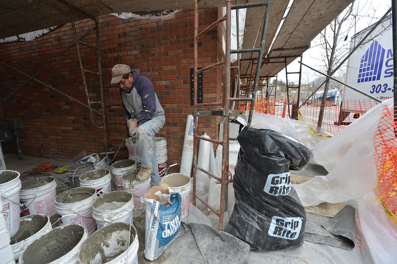 Leo Rosoas mixes pastie, gray, concrete-like substance to resurface the wall behind him along Elkhorn Avenue on Saturday. The work is evidence of continued improvement in at least the local economy.
