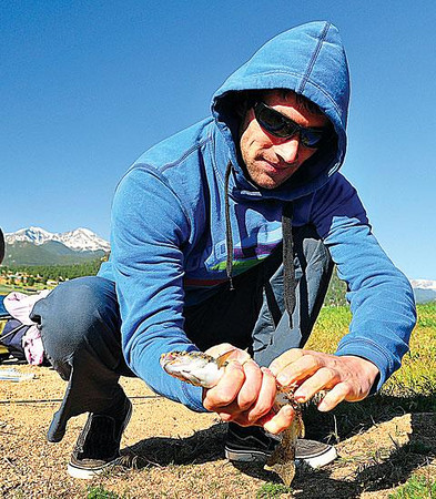 Gotcha! Emilio Kolevski brushes dirt off of his catch at the Lake Estes Fishing Derby on Saturday. The derby was on the third day of Kolevski's visit to the U.S. from Bulgaria. Photo by Walt Hester