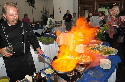 Chef Marc Grandmaison excites attendees with his preparation of Fresh Berriies Romanoff at the Lake Shore Lodge in Estes Park on Tuesday evening. The event celebrated the opening of the Shores Restaurant and a new menu created by Grandmaison and fellow chef Amanda Williams. Photo by Walt Hester.
