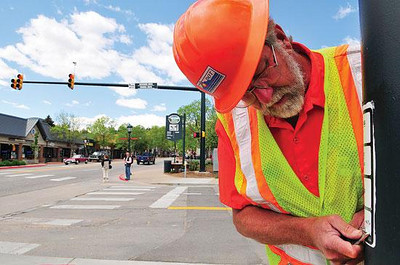 Last little bit Bruce Shepperd of the Colorado Department of Transportation peels an old sign off of a traffic signal pole at Riverside and Elkhorn Avenue on Wednesday. The signs needed to be replaced since the intersection was reconfigure, but temperatures were too cold to adhere new signs explaining the crosswalk buttons. Photo by Walt Hester