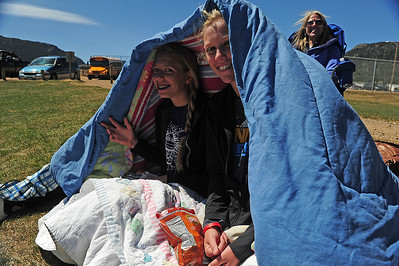 Walt Hester | Trail Gazette Kendra Bellmann and Alli Smith huddle under a blanket at Saturday's baseball game. With little to block the wind, spring sports can get chilly at the Stanley Park ball fields.