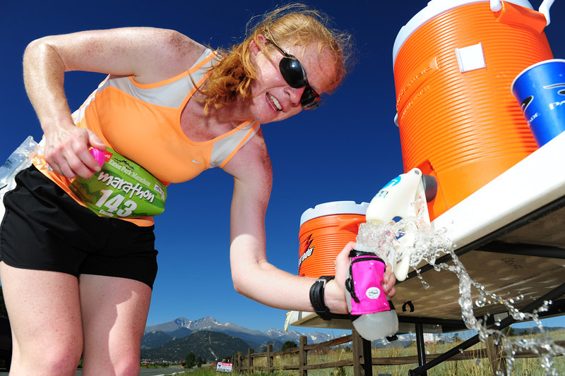 Walt Hester | Trail Gazette<br /> Eventual women's marathon winner Cassie Sonnenberg refills her hydration bottle during the hot and windy race on Sunday. Unusually warm and windy weather took its toll on the runners of Sunday's races.