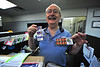 "Larry Hasennkamp shows off ""Forever"" stamps at the post office on Tuesday. Hasennkamp sells his last stamps this week, as he retires on Friday."