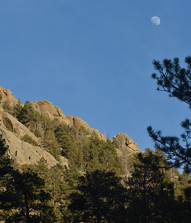 The moon arches over Lumpy Ridge on Wednesday. The ridge is known for its cliffs and buttresses and is popular among rock climbers.