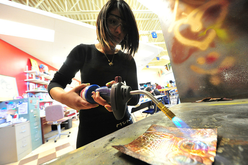 Pricilla Martinez, 15, applies heat to copper foil in the EStes Park High School's art room on Wednesday. Students were creating relief sculpture on the foil and using the heat to alter the color of the foil.