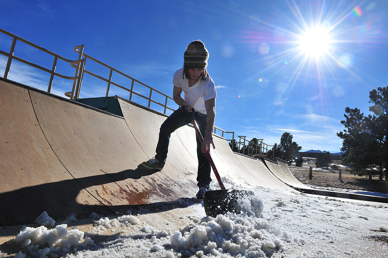 Nick Pyle of Birlington, Iowa, scoops melting snow off of the ramps and quarter pipes at the Estes Valley Skate Park on Wednesday. Temperatures were 50 degrees warmer on Wednesday afternoon than Monday morning.