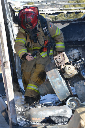 Estes Park firefighter Derek Rosenquist takes images of a piece of equipment inside a truck at the YMCA of the Rockies on Thursday. Firefighters guess that some piece of equipment inside the truck ignited the fire on Thursday, but an official cause has not been determined.