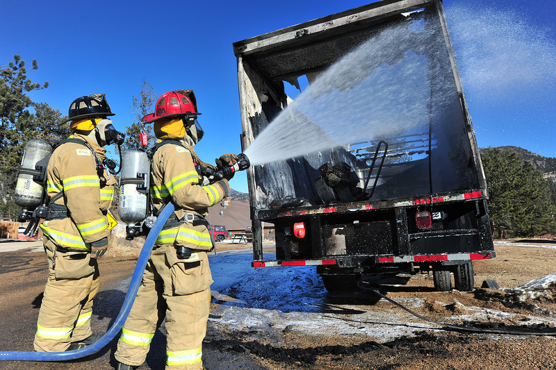 Estes Park firefighters spray a truck at the YMCA of the Rockies on Thursday. The truck caught fire while parked near a wood structure, then was driven away from the building before firefighters began putting the fire out.