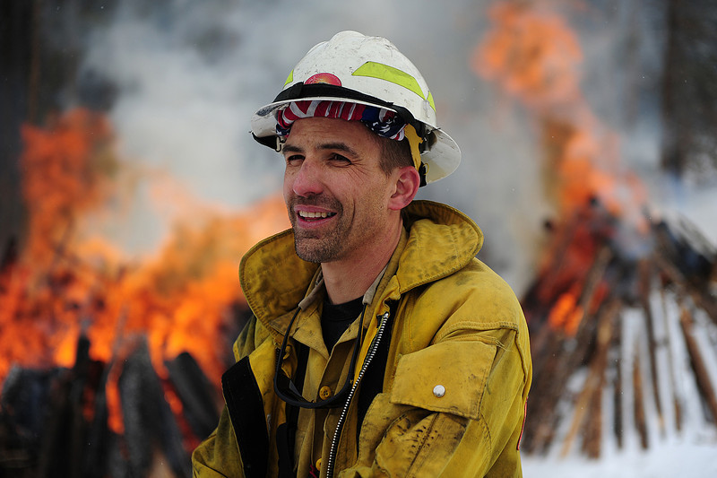 Walt Hester   Trail Gazette<br /> Fuels specialist Doug Watry answers questions on Thursday morning about the large slash piles burning behind him. New snow and calm winds made for perfect slash burning opportunities in the national park.