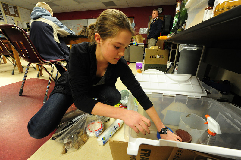 Walt Hester | Trail Gazette<br /> Lily Tomasula Martin, 11, packs a box with components to create a natural water filter. Rocks, pebbles and charcoal all help in the Science Olympiad project.