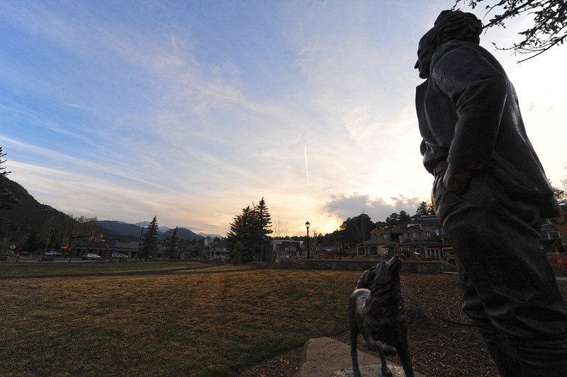 Walt Hester | Trail Gazette<br /> The statue of Enos Mills watches the sky change colors as the sun sets onTuesday. More clouds are expected over the weekend in Estes Park.
