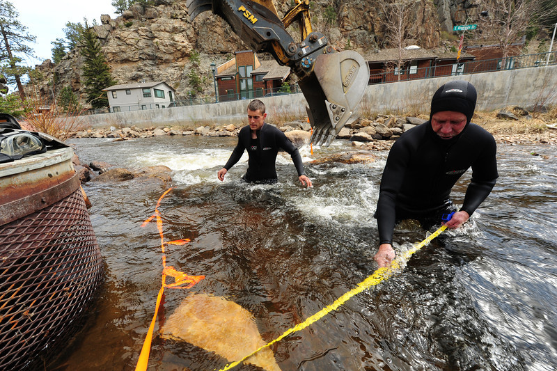Walt Hester | Trail Gazette<br /> Mike Atkins, right, and son, Jarred, clean out an intake in the Big Thompson River on Wednesday. The intake supplies water for the fountains in Riverside Plaza.