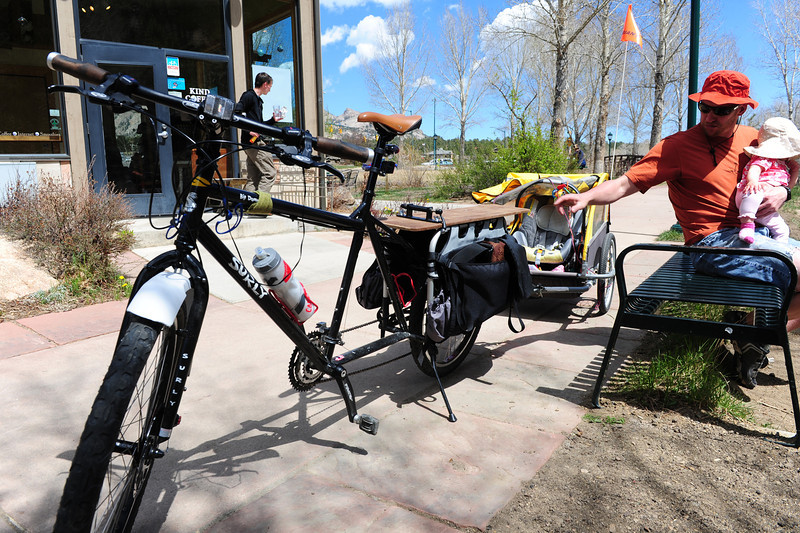 Walt Hester | Trail Gazette<br /> Zach Zehr, with daughter, Carsyn, enjoy a sunny Sunday along the Riverwalk. With gas prices on the rise and global demand on the rise, Zehr's mode of transportation might be a good way to go this summer.
