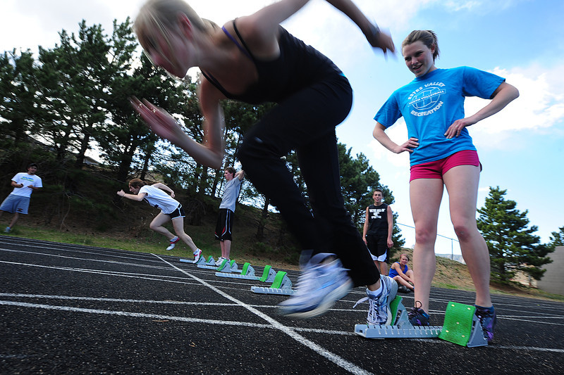 Walt Hester | Trail Gazette<br /> Faith Weibel, left, holds the blocks as Sara Speedlin explodes out during Wednesday's pre-league meet practice. The team headed to Eaton on Thursday for the Patriot League championship meet.