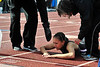 Walt Hester | Trail Gazette<br /> Erin Barker gets a little help after diving for the finish line after te 4x400 meter relay. Barker put in a courageous effort to bump the team up a place, even sacrificing a little skin.